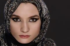 一张美丽的阿拉伯妇女面孔的一张正面图的画象与一条顶头围巾的 免版税库存图片
