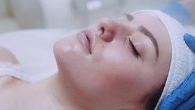 一张美丽的female's面孔的极端接近的视图与被清洗与在秀丽温泉的蒸汽疗法的闭合的眼睛的 股票录像