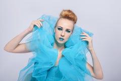 一张蓝色纱出王牌的典雅的美丽的妇女 免版税库存图片