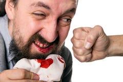 掴一张血淋淋的嘴的ManÂ的拳头 免版税图库摄影