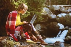 一张被定调子的画象戴眼镜的一个微笑的自由职业者行家女孩在有膝上型计算机下跪坐的一条毯子穿戴了 图库摄影