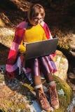 一张被定调子的画象戴眼镜的一个微笑的自由职业者行家女孩在有膝上型计算机下跪坐的一条毯子穿戴了 免版税库存图片