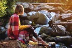 一张被定调子的画象戴眼镜的一个微笑的自由职业者行家女孩在有膝上型计算机下跪坐的一条毯子穿戴了 免版税库存照片