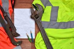 一张被弄皱的纸片与绿色和橙色运转的制服和可调扳手围拢的两支铅笔的 静物画  免版税库存图片