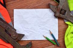 一张被弄皱的纸片与绿色和橙色运转的制服和可调扳手围拢的两支铅笔的 静物画  库存图片