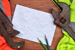 一张被弄皱的纸片与绿色和橙色运转的制服和可调扳手围拢的两支铅笔的 静物画  免版税库存照片