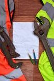 一张被弄皱的纸片与绿色和橙色运转的制服和可调扳手围拢的两支铅笔的 静物画  免版税图库摄影
