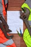 一张被弄皱的纸片与绿色和橙色运转的制服和可调扳手围拢的两支铅笔的 静物画  库存照片