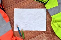一张被弄皱的纸片与绿色和橙色运转的制服围拢的两支铅笔的 静物画与修理相关,镭 库存图片