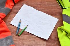 一张被弄皱的纸片与绿色和橙色运转的制服围拢的两支铅笔的 静物画与修理相关,镭 免版税图库摄影