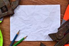 一张被弄皱的纸片与绿色围拢的两支铅笔的a 库存图片