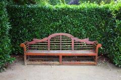 公园长椅在修剪的花园庭院里 免版税库存照片