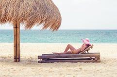 一张轻便折叠躺椅的女孩在海滩 库存照片