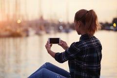 一张年轻女性制造的照片的后面看法与她的手机数字照相机的,当放松在新鲜空气在夏天晚上时, 免版税库存图片