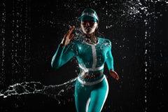 一强运动,妇女短跑选手,跑在佩带在薄荷的颜色sportswea的黑背景 库存图片