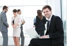 一微笑的商人sittingwith同事workin的画象 库存照片