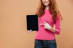 一微笑的年轻红头发人女孩指向的播种的图象 免版税库存照片