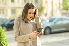 一微笑的愉快的年轻女人的室外画象有智能手机的,城市街道背景,秋天好日子 女孩情感地起反应 免版税库存照片