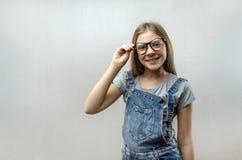 一微笑的美丽的少女的画象戴眼镜的 E ?? 库存照片