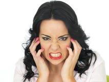 一恼怒沮丧年轻西班牙妇女握紧的画象 免版税库存照片