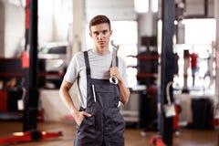 一悦目automechanic站立在与一把板钳的一汽车修理服务在他的手上 免版税库存照片