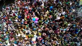 一愉快的女孩少年挥动的手和送在Holi期间的一个飞吻的空中射击上色节日有以下看法  图库摄影