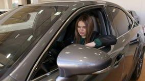 一愉快的少女的画象在售车行中的驾驶一辆新的汽车 影视素材