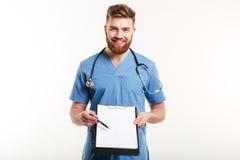 一愉快的男性医生或医疗护士指向的画象 免版税库存照片