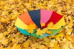 一把五颜六色的伞在秋天的雨中离开 免版税库存图片