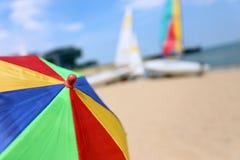 一把五颜六色的沙滩伞的上面反对天空的和小船和海 库存图片