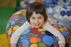 一把五颜六色的被填塞的凳子的小女孩 图库摄影