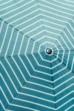 一把伞的特写镜头有白色条纹的在天蓝色颜色 免版税库存图片