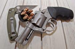 一把刀子、速度装载者和一把左轮手枪在一张白色桌上 免版税图库摄影