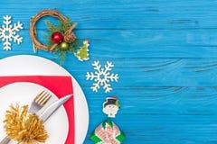 一把刀子和叉子在白色板材在用圣诞节装饰的红色餐巾缠绕木雪花和礼物盒 免版税库存图片
