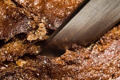 一把刀子的刀片在黑麦面包宏指令外壳的  库存照片