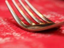 一把叉子的尖叉的宏指令与红色桌布的 库存照片
