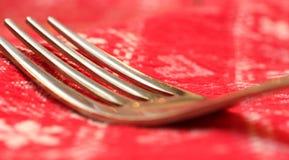 一把叉子的尖叉的宏指令与红色桌布的 图库摄影