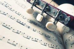 一把吉他的头和钉在音乐笔记的 免版税库存照片