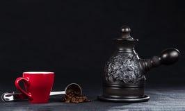 一把咖啡壶、杯子和钢量匙用咖啡豆 免版税库存图片