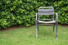 一把唯一老钢椅子在庭院里 库存照片