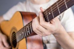 一把声学吉他的图片,古典颜色,在吉他弹奏者的手上 库存图片