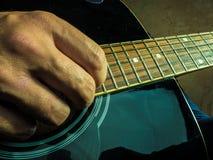 一把声学吉他的特写镜头照片由一个人使用了 免版税库存图片