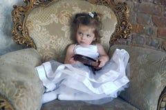 一把大古色古香的椅子的小女孩 免版税库存照片