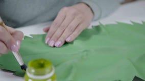 一把妇女艺术家扣篮刷子的特写镜头在树胶水彩画颜料油漆和工艺的 股票视频