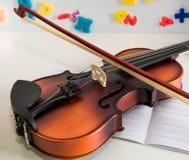 一把小儿童` s小提琴和弓在儿童` s学习书桌 免版税库存图片