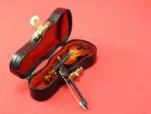 一把微型小提琴的特写镜头在它的黑盒里面的,桃红色表面上 图库摄影
