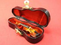 一把微型小提琴的特写镜头在它的黑盒里面的,桃红色表面上 库存图片