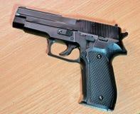 一把手枪的塑料复制品木表面上的 免版税库存图片