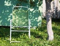 一把扶手椅子在一棵树下在庭院里 库存照片