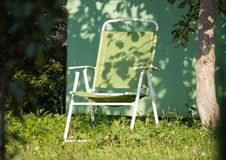 一把扶手椅子在一棵树下在庭院里 免版税库存图片